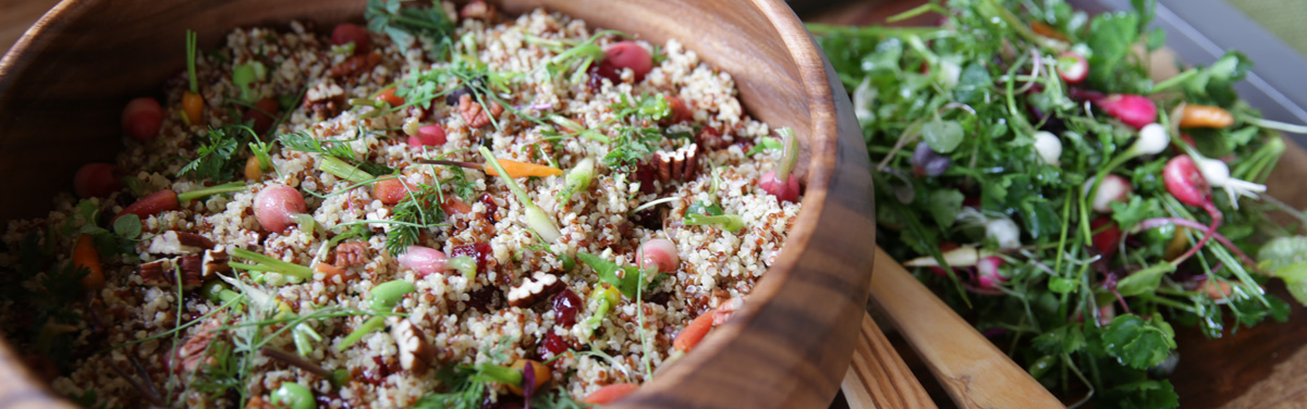 Couscous with carrots and herbs inside of a wooden bowl beside a spring salad