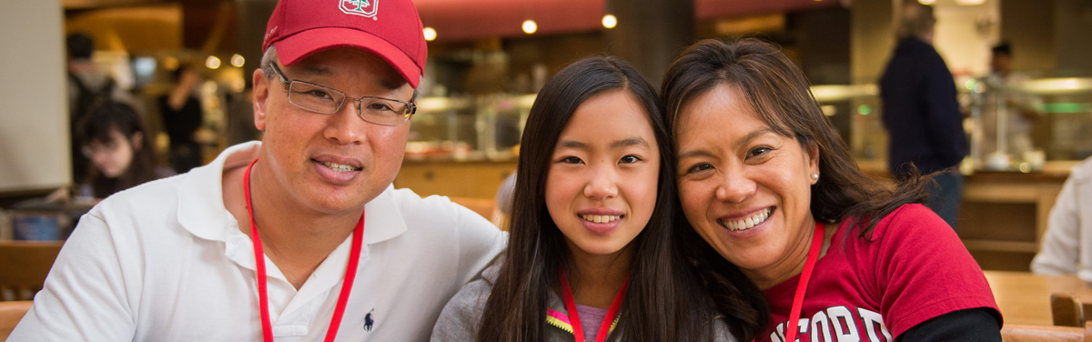 A mother and father sitting and smiling with their daughter at a table inside of the Arrillaga Family Dining Commons
