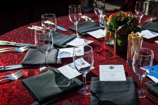 Stanford Catering table setup with red linen, black napkins and silverware.