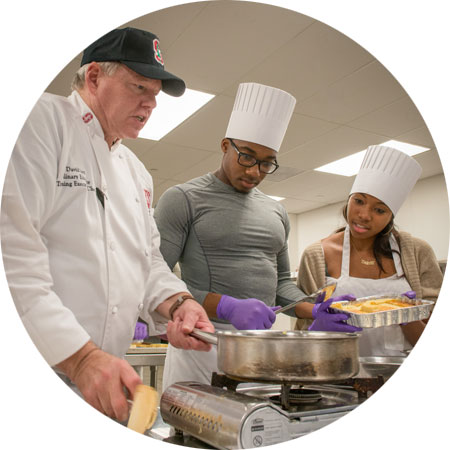 David Iott teaching two students in the Teaching Kitchen