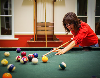 Student playing a game of pool at The Axe and Palm.