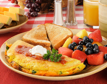 A breakfast plate with toast, fruit and eggs.