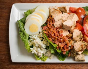 Olives catering includes fresh salad like this cob salad with bacon and chicken
