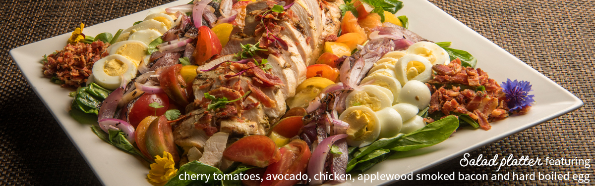 Salad platter featuring cherry tomatoes, avocado, chicken, applewood smoked bacon and hard boiled egg