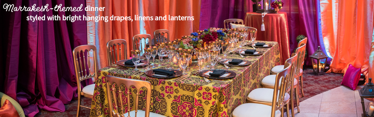 Marrakesh-themed dinner styled with bright hanging drapes, linens and lanterns