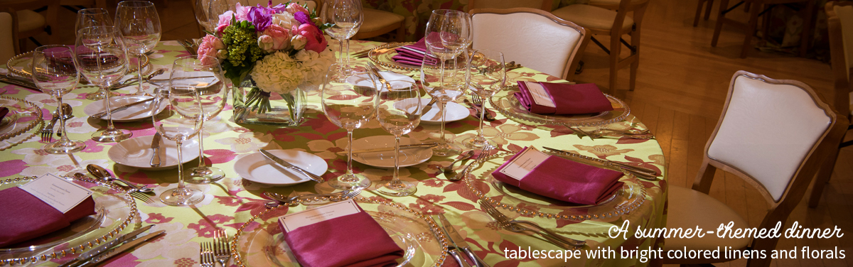 A summer-themed dinner tablescape with bright colored linens and florals