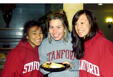 Three students with a plate of food in the dining hall
